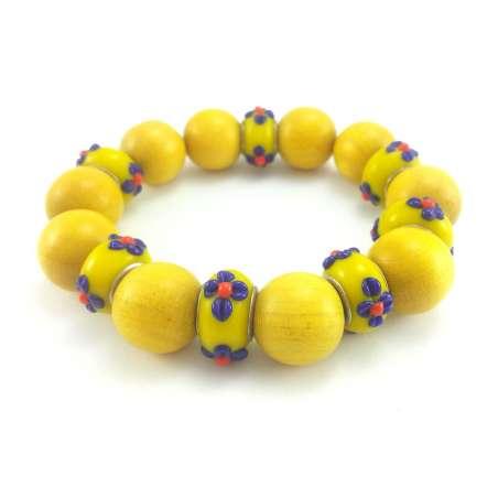 Żółta bransoletka z drewna i korali modułowych ze szkła weneckiego w kwiaty.