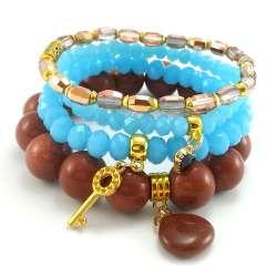 Komplet bransoletek z piaskiem pustyni, kryształkami szklanymi i złotymi zawieszkami charms.
