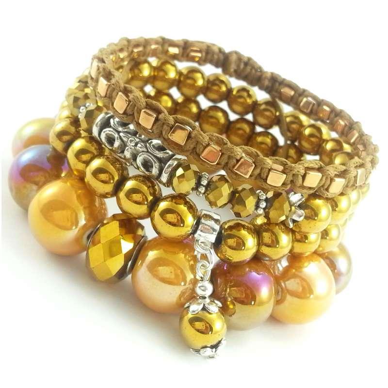 Zestaw bransoletek ze złotych kamieni hematytu, ceramiki, kryształków i bawełny.